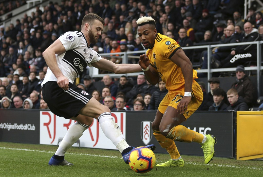 Fulham's Calum Chambers, left, and Wolverhampton Wanderers' Adama Traore battle for the ball during the English Premier League soccer match at Craven ...