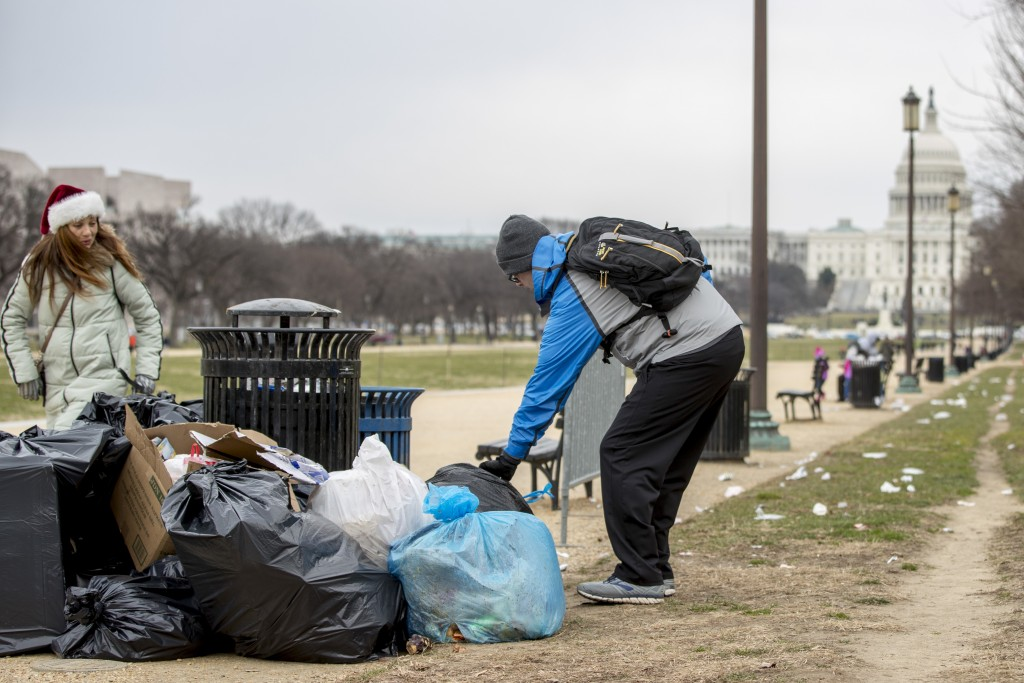 The Capitol building is visible as a man who declined to give his name picks up garbage and stacks it near a trash can during a partial government shu...