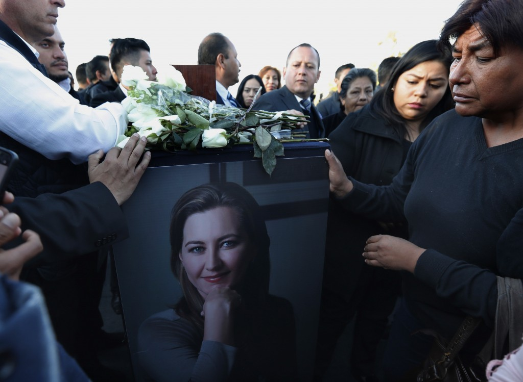 Relatives and friends surround the urn with ashes of opposition Puebla state Gov. Martha Erika Alonso during a farewell ceremony in Puebla City, south
