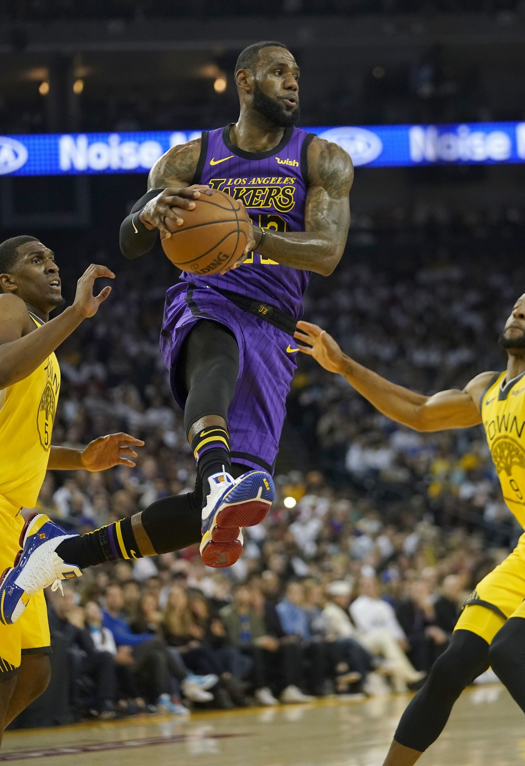 Los Angeles Lakers forward LeBron James (23) drives between Golden State Warriors' Kevon Looney (5) and Andre Iguodala during the first half of an NBA...