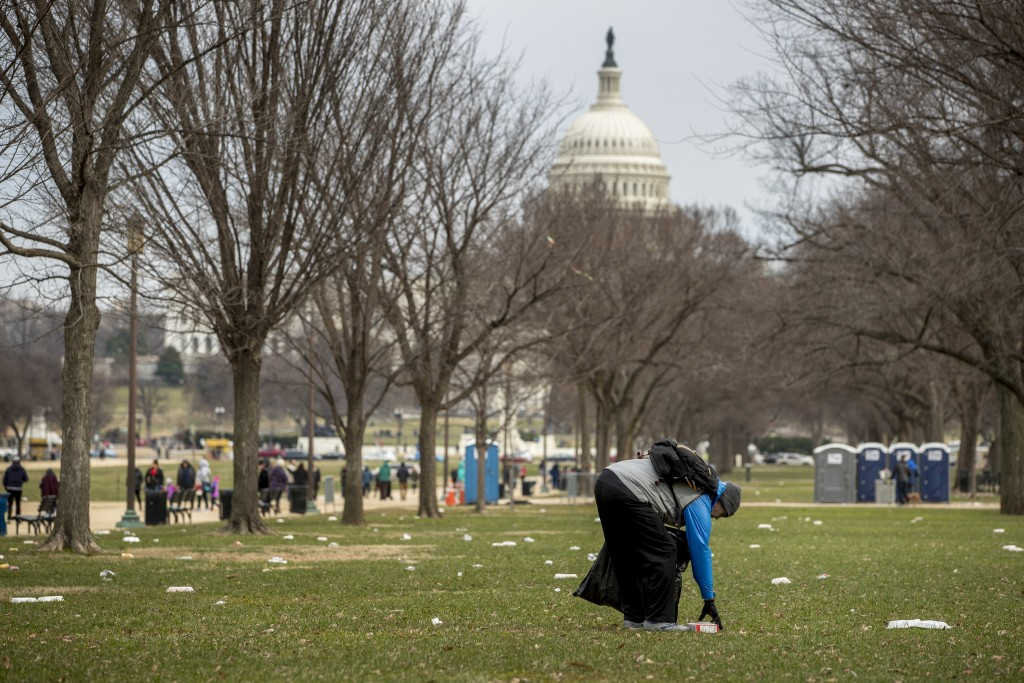 The Capitol building is visible as a man who declined to give his name picks up garbage during a partial government shutdown on the National Mall in W...