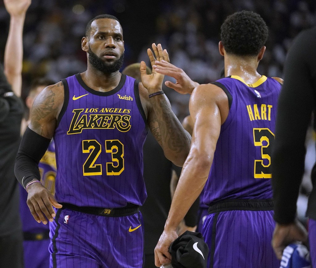 Los Angeles Lakers forward LeBron James (23) high-fives Josh Hart (3) at the end of the first half of the team's NBA basketball game against the Golde