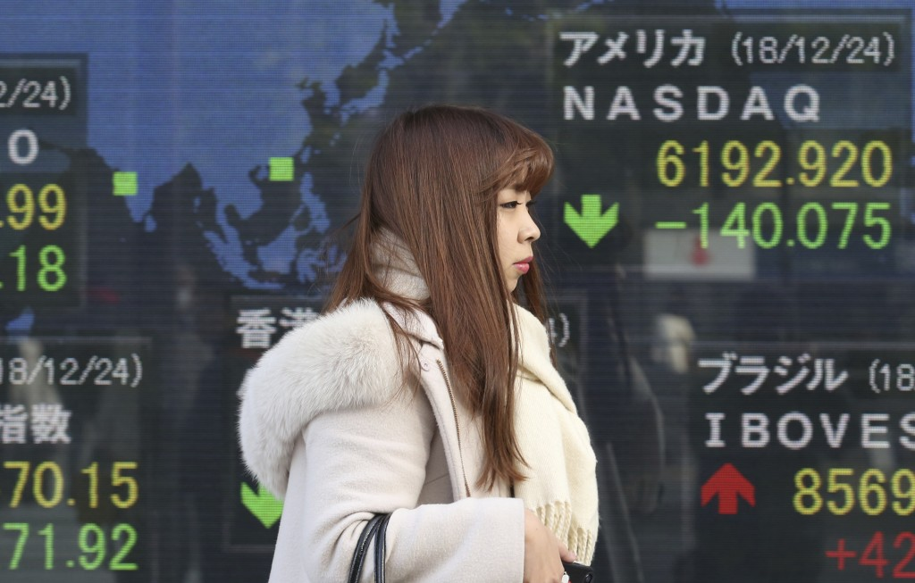 A woman walks by an electronic stock board of a securities firm in Tokyo, Wednesday, Dec. 26, 2018. Asian markets were mostly lower on Wednesday after...