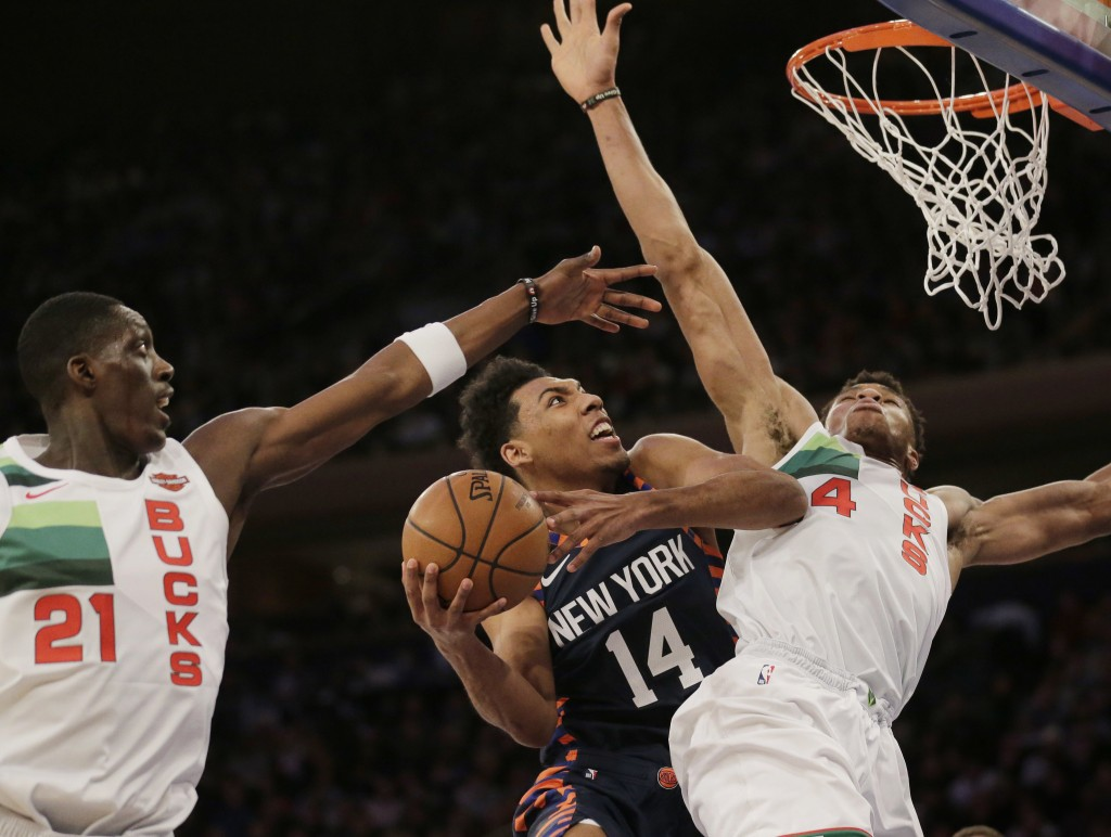 New York Knicks' Allonzo Trier (14) drives past Milwaukee Bucks defenders during the first half of the NBA basketball game, Tuesday, Dec. 25, 2018, in...