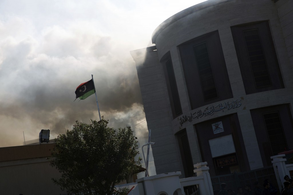 Smoke rises shortly after an attack on the foreign ministry building, in Tripoli, Libya, Tuesday, Dec, 25, 2018. Security officials said Tuesday that ...