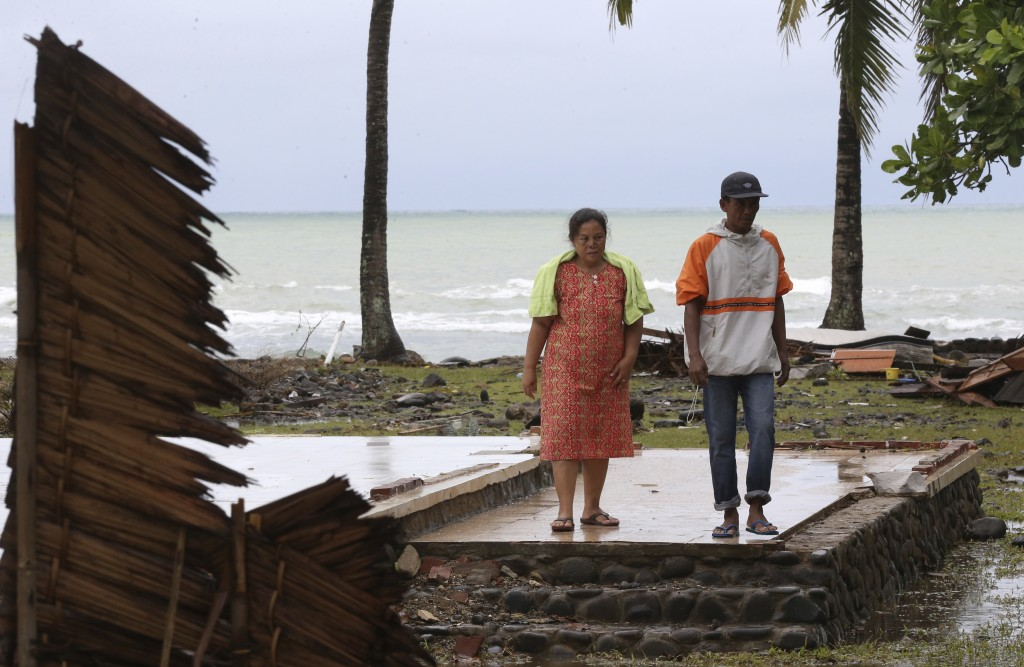 A tsunami survivor Kusmiati walks with her husband Aden at a destroyed villa caused by the tsunami in Carita, Indonesia, Wednesday, Dec. 26, 2018. Ind...