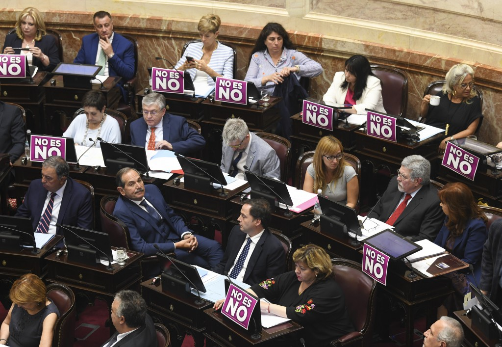 """This Dec. 18, 2018 photo shows placards displayed on the desk of female senators with a message that reads in Spanish: """"No means no"""", during a legisla"""