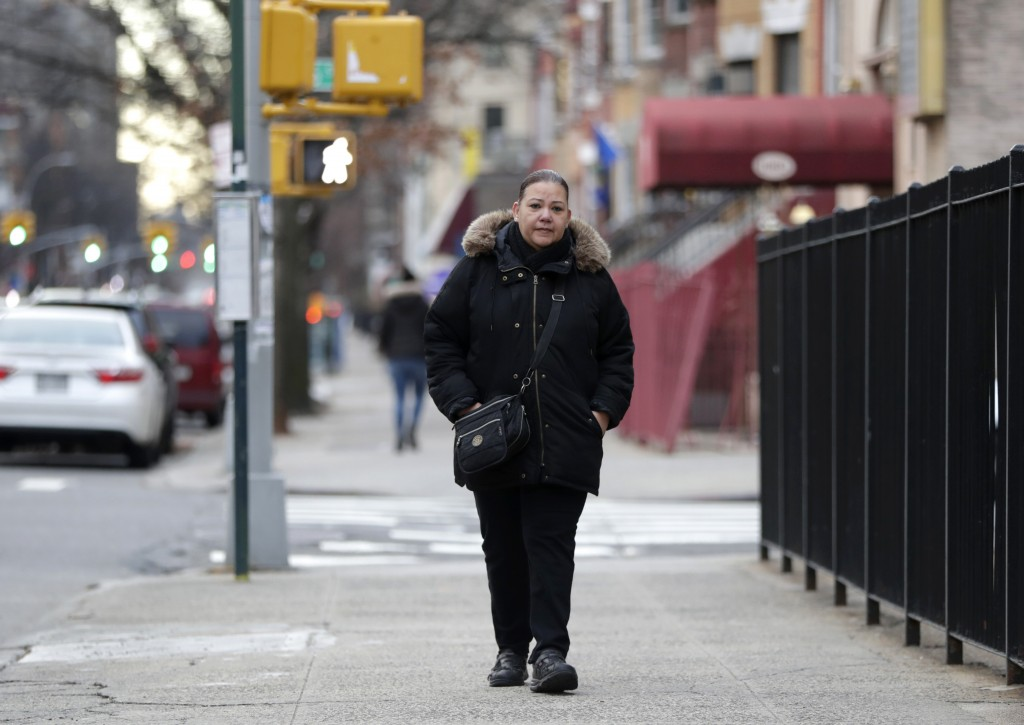 In a photo taken Dec. 23, 2018, Flavia Cabral walks to her mother's home in the Bronx section of New York. Cabral, who works two jobs, will be among m...
