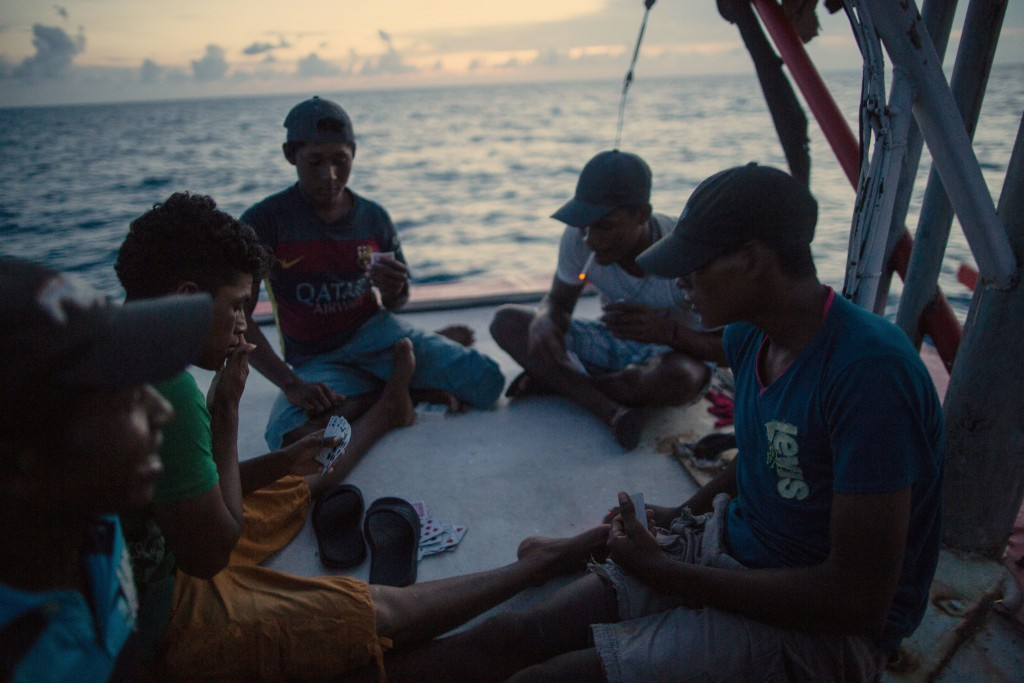 In this Sept. 10, 2018 photo, Miskito divers play a game of cards on a ship's stern as they are transported home after a two week fishing trip, near S...