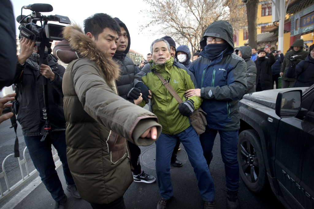 Plainclothes security officers take away a supporter of Chinese human rights lawyer Wang Quanzhang near the Secondary Intermediate People's Court of T...