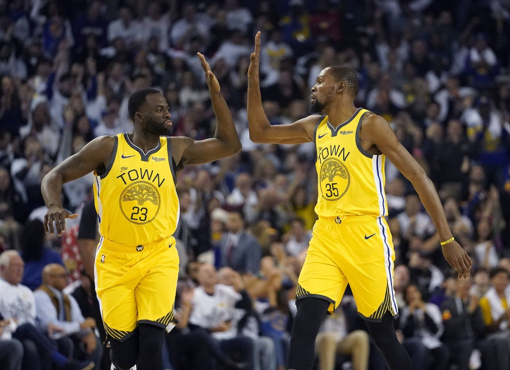 Golden State Warriors forward Draymond Green (23) high-fives Kevin Durant (35) after the latter's 3-point basket against the Los Angeles Lakers during