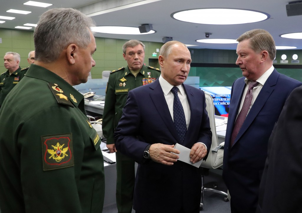 Russian Defense Minister Sergei Shoigu, left, Russian President Vladimir Putin, center, Chief of General Staff of Russia Valery Gerasimov, background