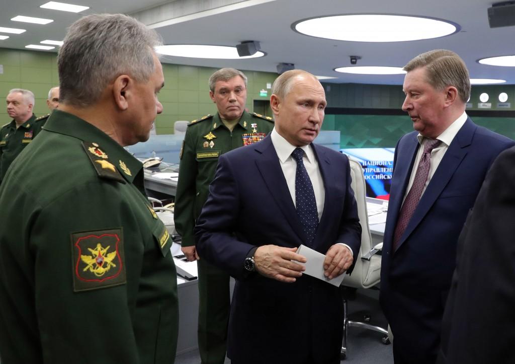 Russian Defense Minister Sergei Shoigu, left, Russian President Vladimir Putin, center, Chief of General Staff of Russia Valery Gerasimov, background ...