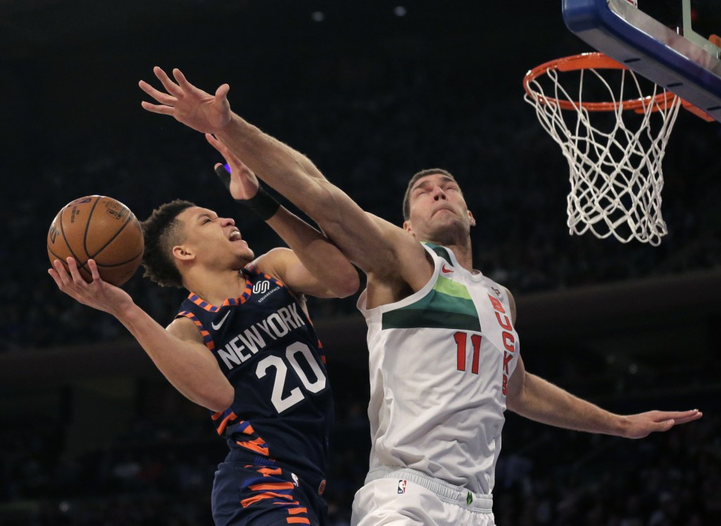 New York Knicks' Kevin Knox, left, drives to the basket past Milwaukee Bucks' Brook Lopez during the first half of the NBA basketball game, Tuesday, D...