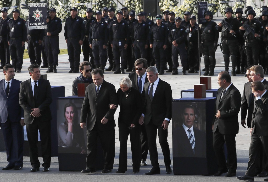 Mexico's Secretary of the Interior Olga Sanchez Cordero, center, stands between urns with ashes of Puebla state Gov. Martha Erika Alonso, left, and he