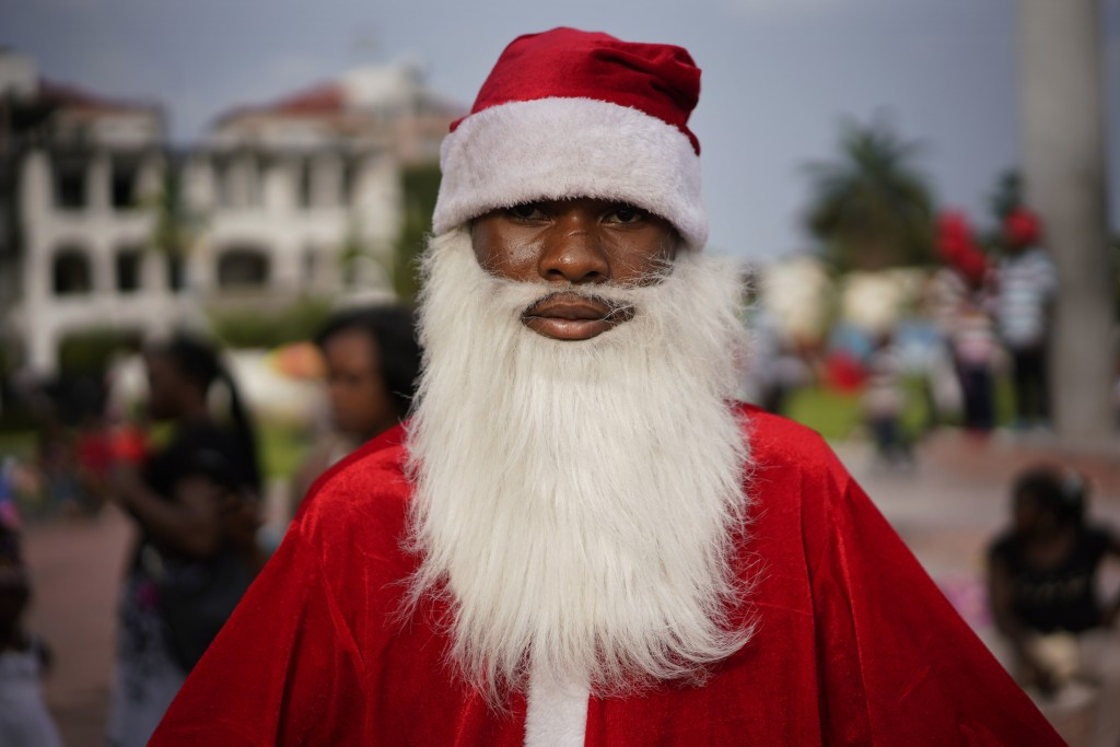 A Congolese Santa Claus waits to pose with children in Kinshasa, Congo, Tuesday Dec. 25, 2018. Traditionally Congolese dress up and take to the parks ...