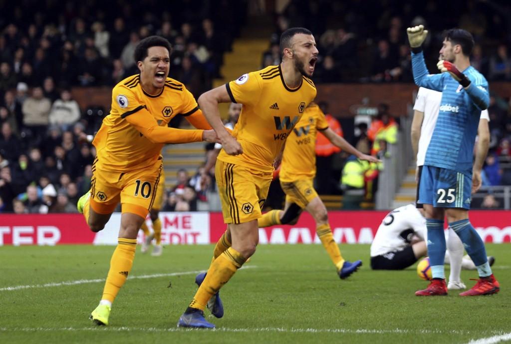 Wolverhampton Wanderers' Romain Saiss, center, celebrates scoring against Fulham during the English Premier League soccer match at Craven Cottage, Lon