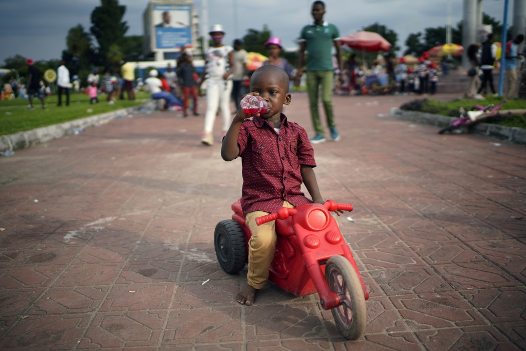 A Congolese child rides his tricycle in Kinshasa , Congo, Tuesday Dec. 25, 2018. Traditionally Congolese dress up and take to the parks on Christmas d...