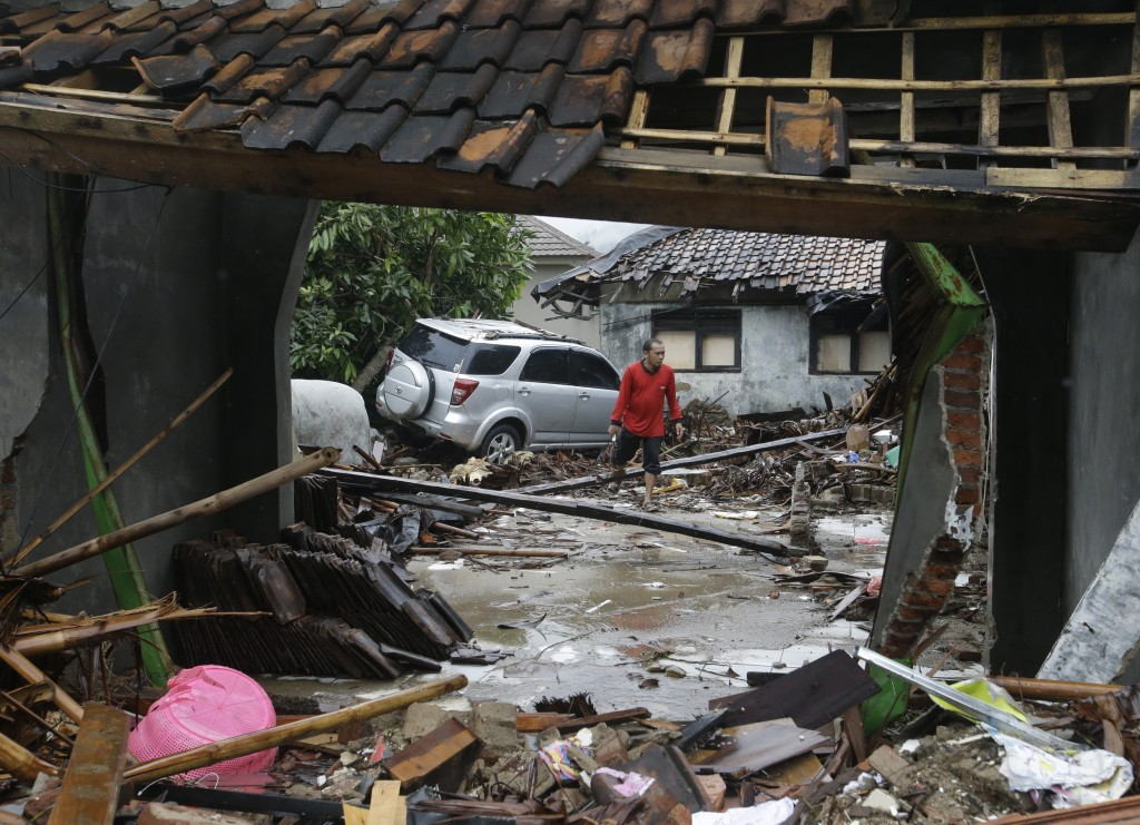In this Wednesday, Dec. 26, 2018, file photo, a man walks near debris at a tsunami-ravaged area in Carita, Indonesia. Indonesian authorities asked peo...