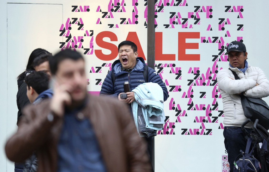 A shopper yawning while waiting outside a shop,  during the Boxing Day sales, on Oxford Street, in London,  Wednesday, Dec. 26, 2018. (Isabel Infantes