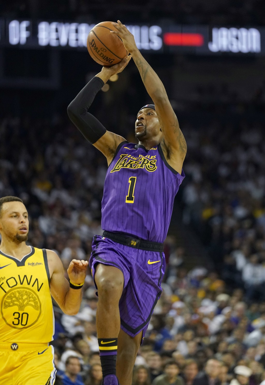 Los Angeles Lakers guard Kentavious Caldwell-Pope (1) shoots next to Golden State Warriors guard Stephen Curry (30) during the first half of an NBA ba...