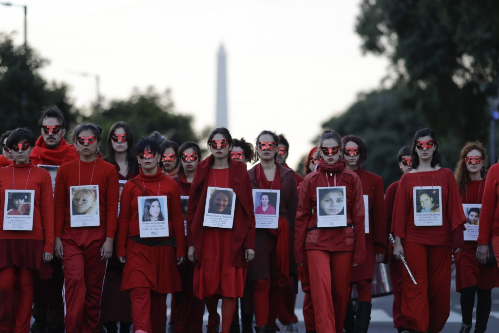 FILE - In this June 3, 2017 file photo, women hold pictures of victims of gender violence during a protest in Buenos Aires, Argentina. Under the hasht...