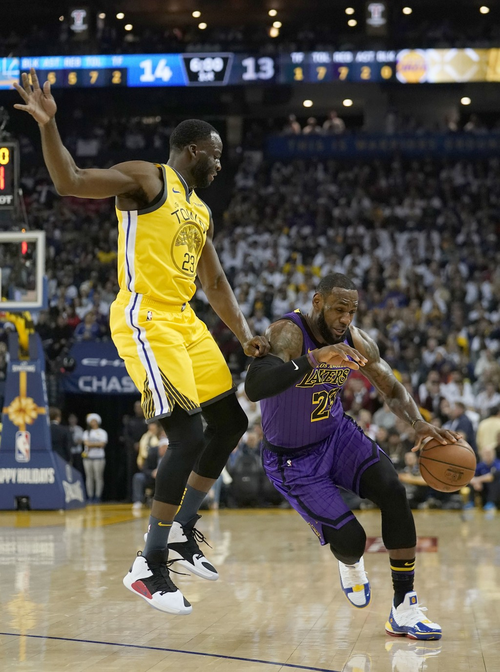 Golden State Warriors forward Draymond Green (23) fouls Los Angeles Lakers forward LeBron James (23) during the first half of an NBA basketball game T...