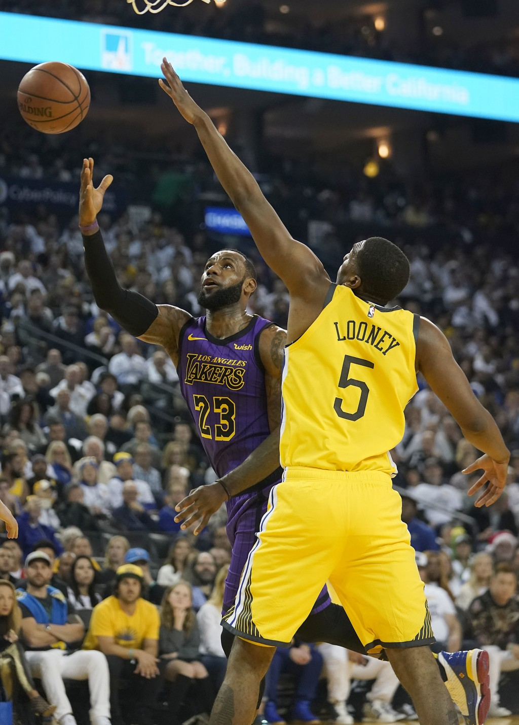 Los Angeles Lakers forward LeBron James (23) drives to the basket against Golden State Warriors forward Kevon Looney (5) during the first half of an N...