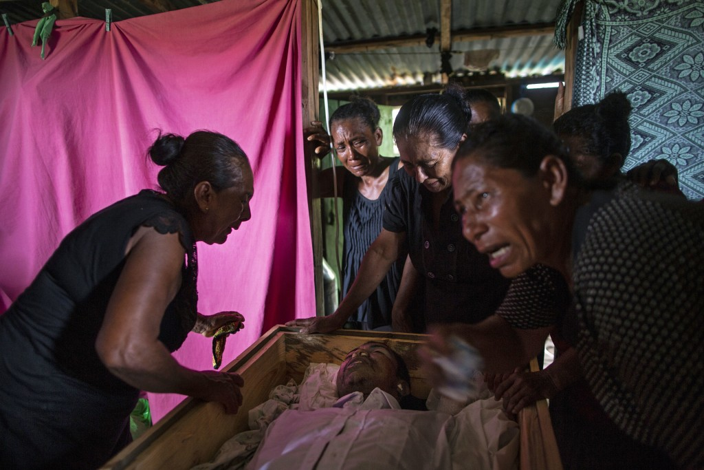 In this Sept. 2, 2018 photo, Sonia Wills, left, accompanied by relatives, mourns over the coffin that contains the remains of her 31-year-old son Misk...
