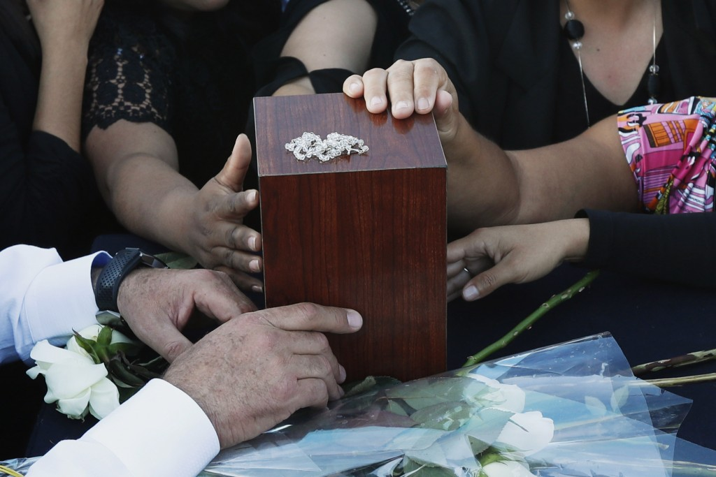 Relatives and friends touch the urn with ashes of opposition Puebla state Gov. Martha Erika Alonso during a farewell ceremony in Puebla City, southeas