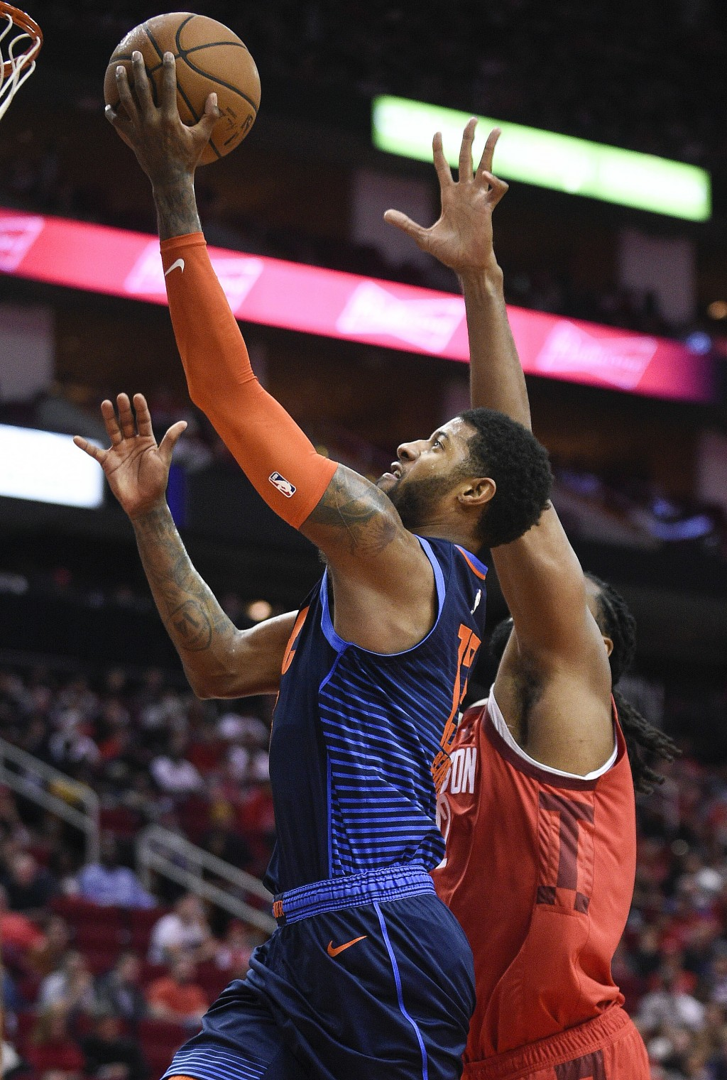 Oklahoma City Thunder forward Paul George, left, drives to the basket past Houston Rockets center Nene Hilario during the first half of an NBA basketb...