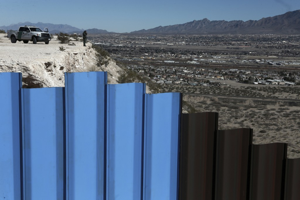FILE - In this Jan. 25, 2017, file photo, an agent from the border patrol, observes near the Mexico-US border fence, on the Mexican side, separating t