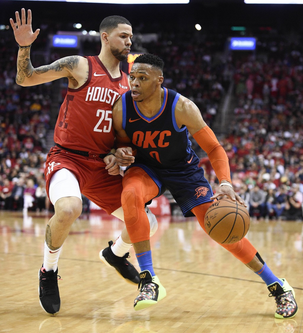 Oklahoma City Thunder guard Russell Westbrook, right, dribbles past Houston Rockets guard Austin Rivers, left, during the first half of an NBA basketb...