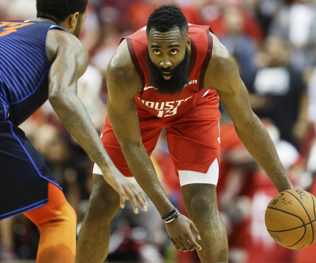 Houston Rockets guard James Harden, right, dribbles as Oklahoma City Thunder forward Paul George defends during the second half of an NBA basketball g...