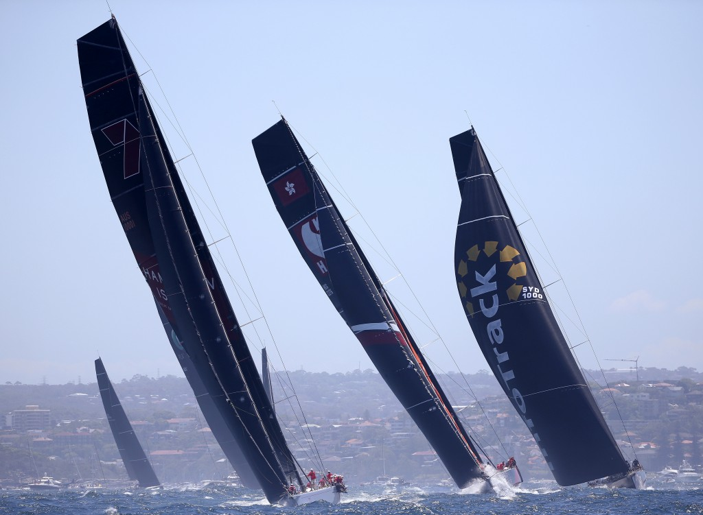 Maxi yachts Wild Oats XI, left, Scallywag and Infotrack, right, leave the heads during the start of the Sydney Hobart yacht race in Sydney, Wednesday,...
