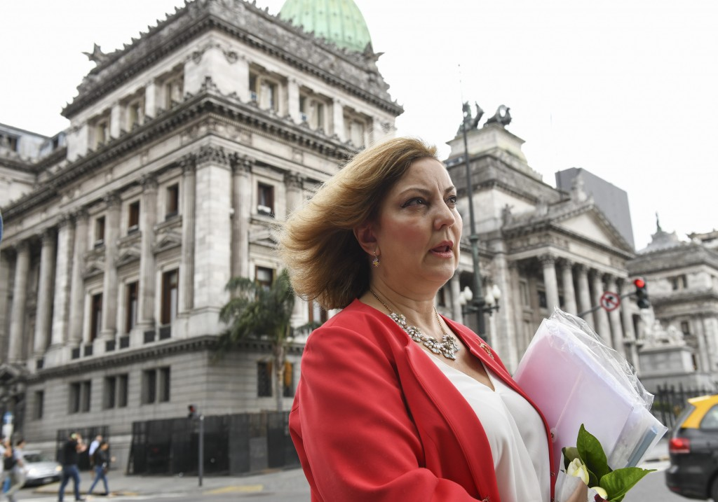 In this Dec. 19, 2018 photo, congressional aide Claudia Guebel speaks while standing outside a justice center, in Buenos Aires, Argentina. Guebel is n