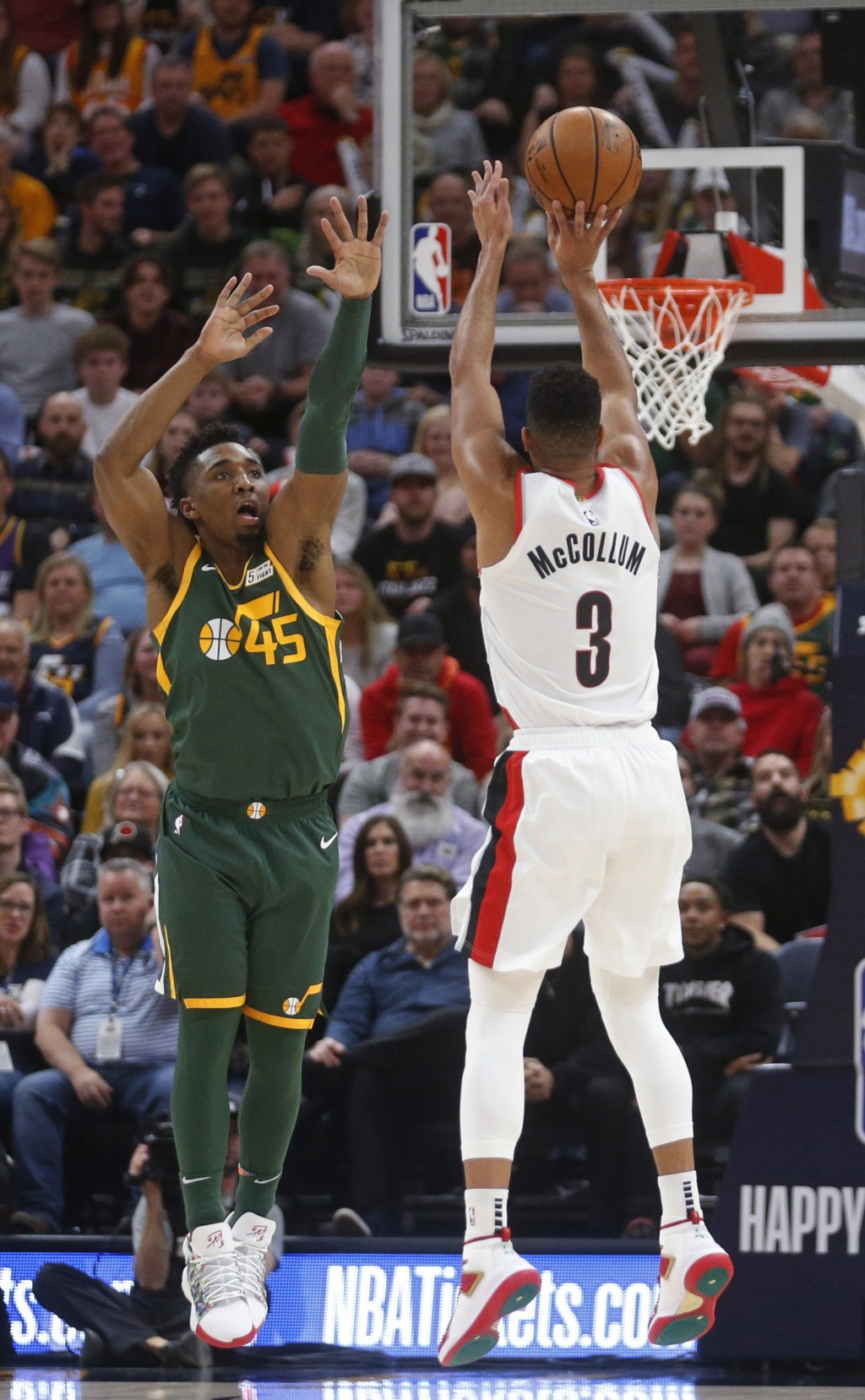 Portland Trail Blazers guard CJ McCollum (3) shoots as Utah Jazz guard Donovan Mitchell (45) defends during the first half of an NBA basketball game T...