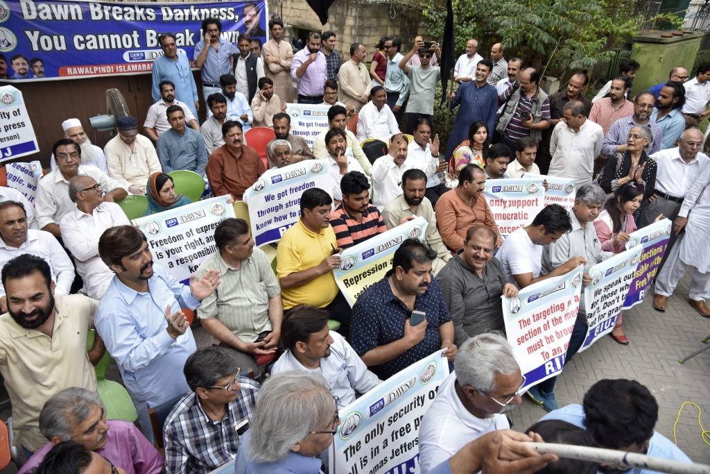 In this July 11, 2018 photo, Pakistani journalists protest against layoffs at newspapers, in Islamabad, Pakistan. Pakistan's military and security age...
