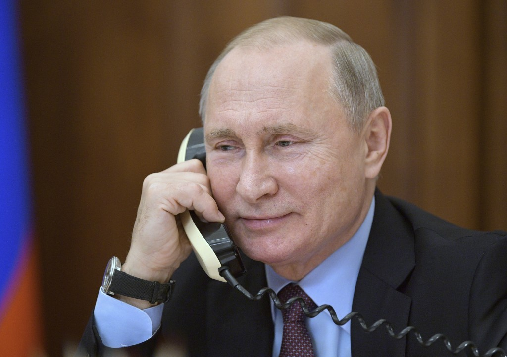 Russian President Vladimir Putin speaks on the phone with a teenager who visited a presidential plane to film its interiors in Luhansk, Russia, Tuesda...