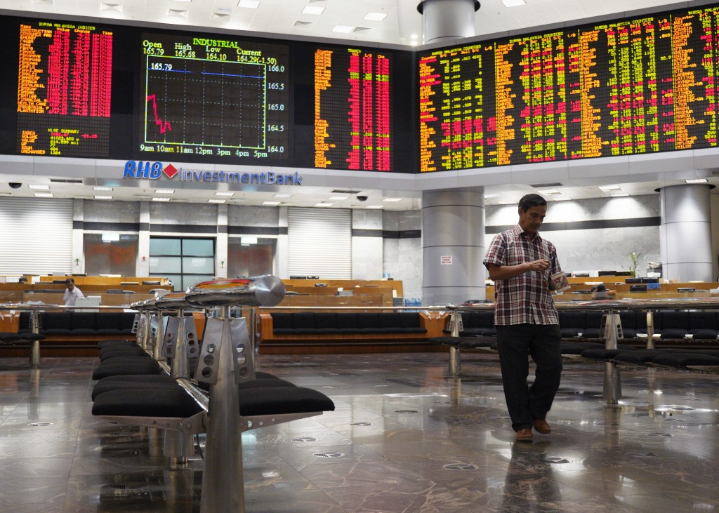 An investor walks in front of private stock trading boards at a private stock market gallery in Kuala Lumpur, Malaysia, Wednesday, Dec. 26, 2018.  Asi