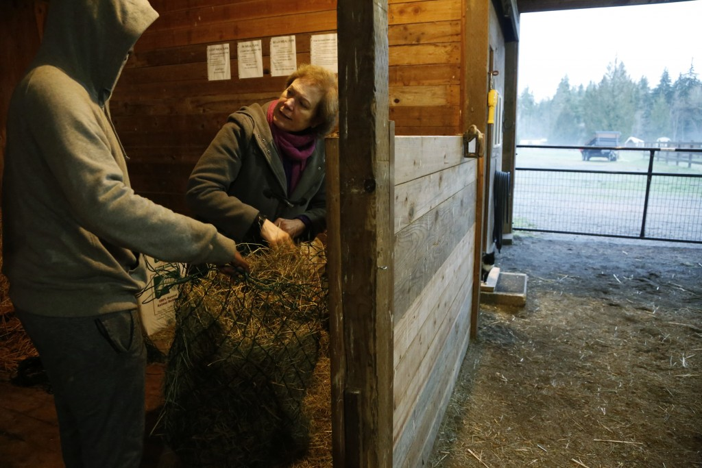 In this Monday, Dec. 10, 2018, photo, Robel, an 18-year-old tech addict from California, left, helps Hilarie Cash load hay to feed the horses at the R...