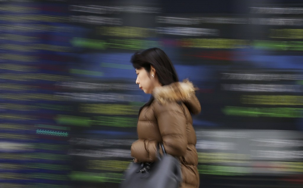 A woman walks by an electronic stock board of a securities firm in Tokyo, Wednesday, Dec. 26, 2018. Asian markets were mostly lower on Wednesday after