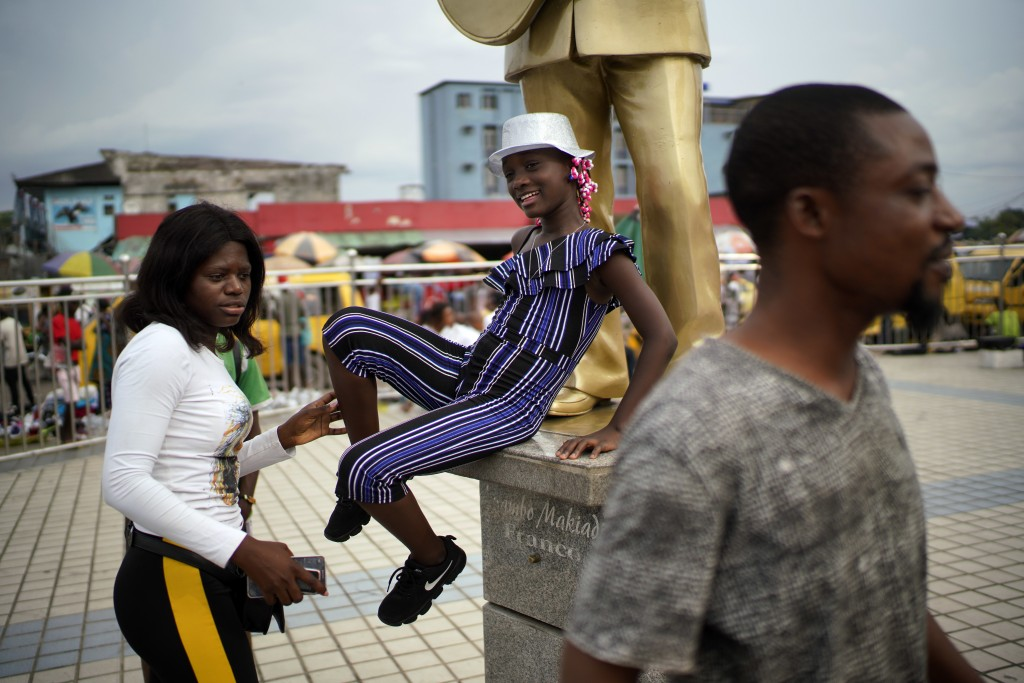Congolese teenagers pose for photographs in Kinshasa , Congo, Tuesday Dec. 25, 2018. Traditionally Congolese dress up and take to the parks on Christm...