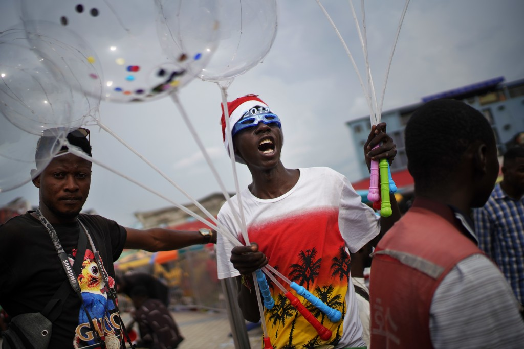 A Congolese man sells balloons in Kinshasa, Congo, Tuesday Dec. 25, 2018. Traditionally Congolese dress up and take to the parks on Christmas day, thi...