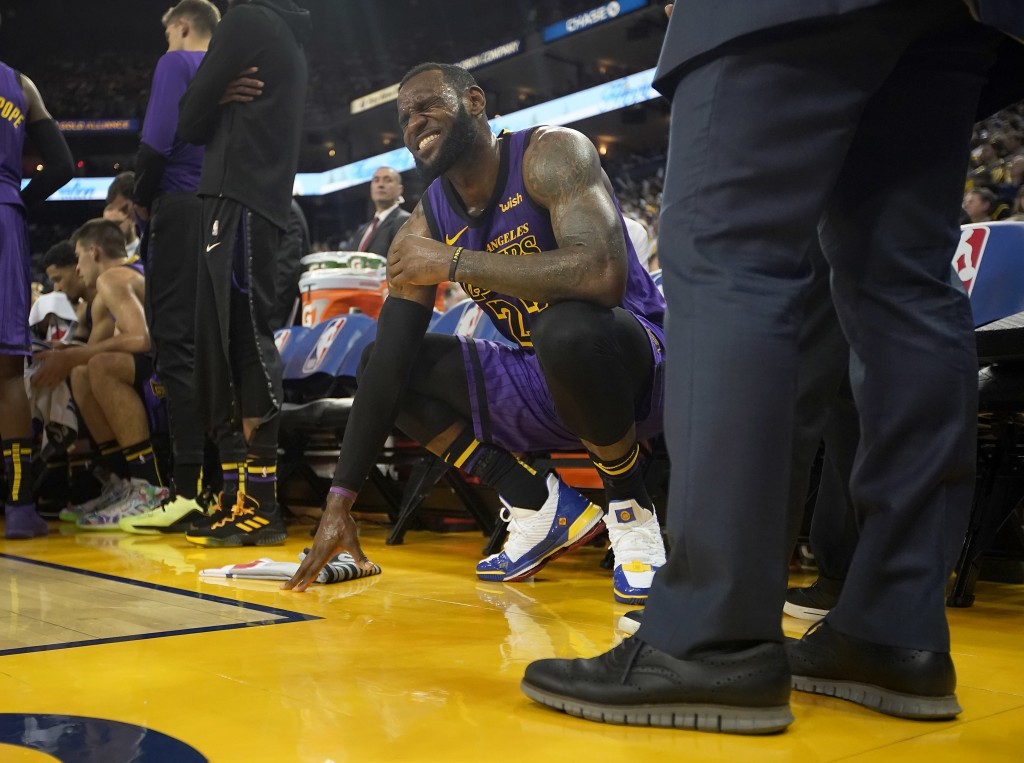 Los Angeles Lakers forward LeBron James (23) grimaces after straining his left groin, during the second half of the team's NBA basketball game against...