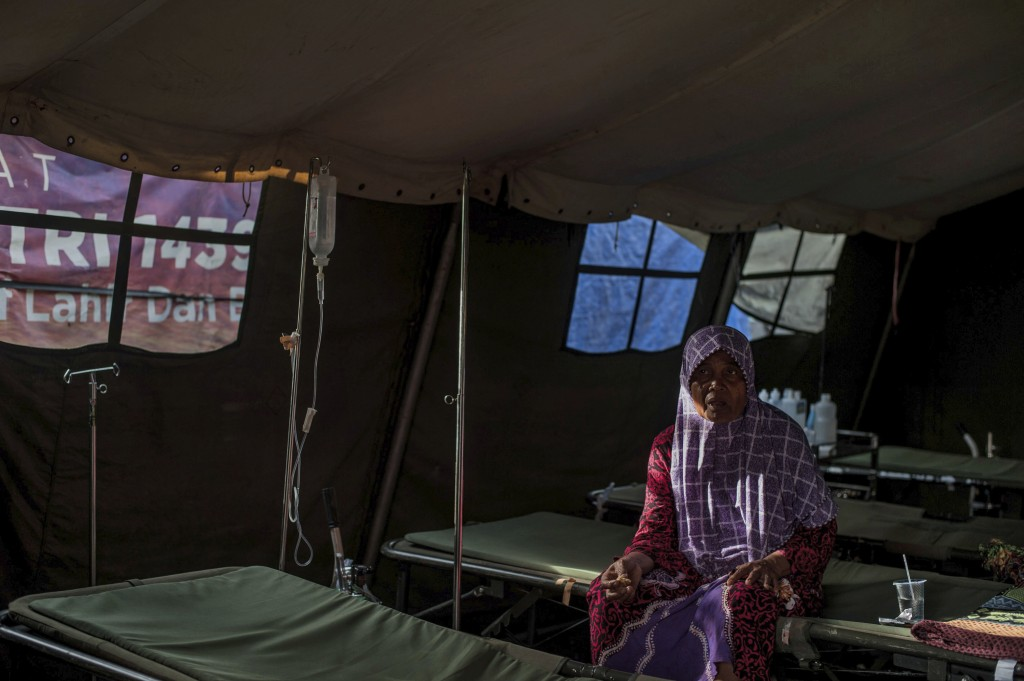 A tsunami survivor sits inside a tent at a makeshift hospital in Labuan, Indonesia, Wednesday, Dec. 26, 2018. Indonesian authorities asked people to a...
