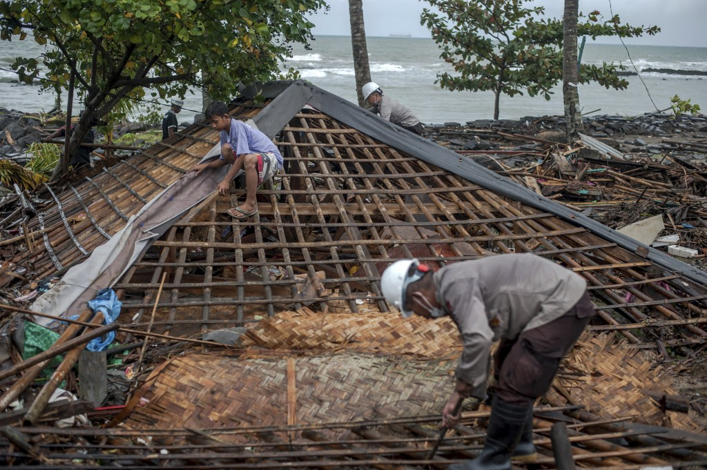Residents, assisted by police officers, clean up debris from the ruin of a house at a neighborhood affected by Saturday's tsunami in Carita, Indonesia...