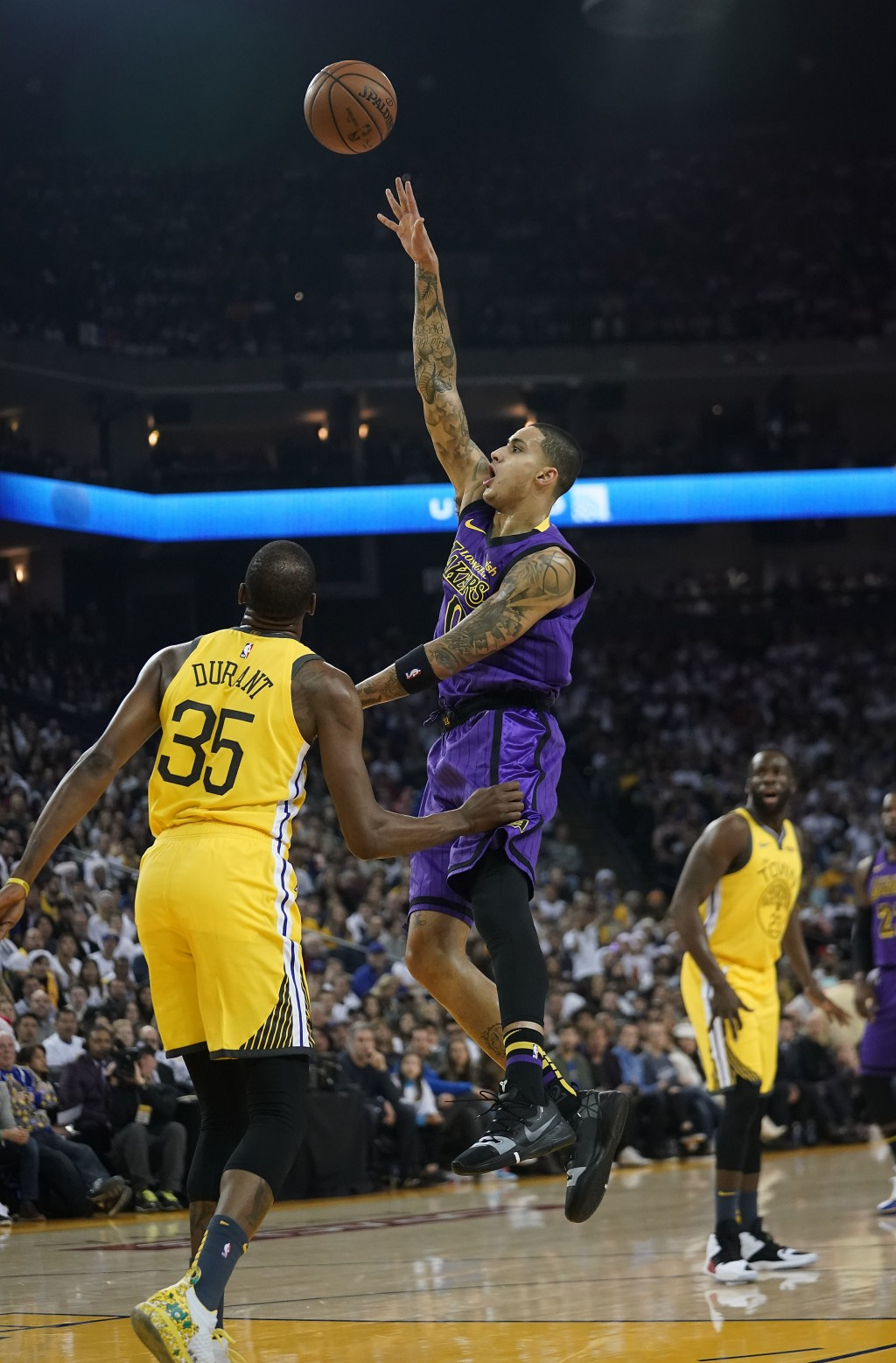 Los Angeles Lakers forward Kyle Kuzma (0) shoots over Golden State Warriors forward Kevin Durant (35) during the first half of an NBA basketball game