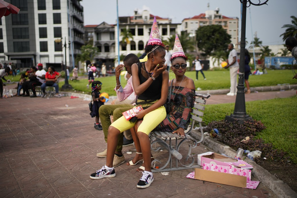 Congolese youth sit on a park bench in Kinshasa, Congo, Tuesday Dec. 25, 2018. Traditionally Congolese dress up and take to the parks on Christmas day...