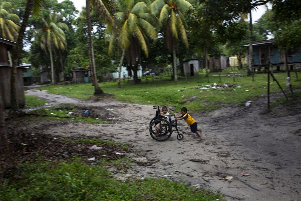 In this Feb. 6, 2018 photo, Charles Melendez, 5, and his 4-year-old brother Jefferson, play with their father's wheelchair while he rests, in Puerto L...